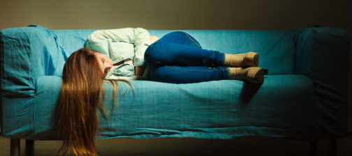Loneliness negative emotion concept. Young sad stressed woman lying on couch at home