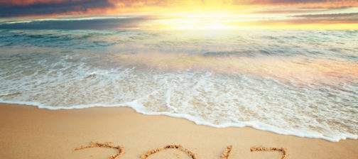 Year 2017 written on sand at sunrise