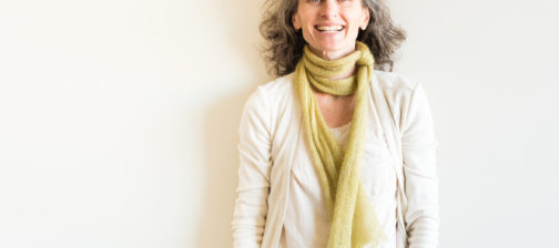 Natural looking middle aged woman with grey hair and green scarf laughing against neutral background